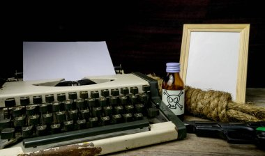 Typewriter with paper page and poison and gun. Concept writer Ro