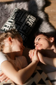 Young Happy Mother and Little Doughter Together. Beautiful Smiling Woman spending time with Cute Adorable Daughter. Mom and Child lying on Bed in Sunlight. Selective focus. Medium sharp. Family and Motherhood Concept