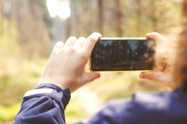 Man making photo on smartphone in forest, smartphone in hands, male photographing on mobile phone