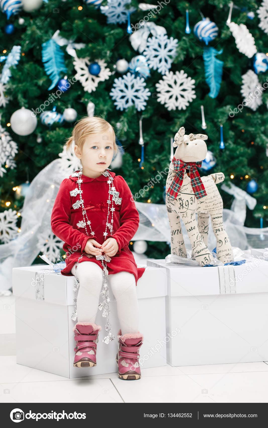 0cb55854a126 Porträtt av blondin kaukasiska baby flicka småbarn med blå ögon i röd  klänning sitter vid nyår