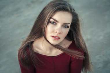Closeup portrait of pensive sad lonely white Caucasian young beautiful woman with green eyes and messy long hair on windy day outdoor at sunset, looking in camera