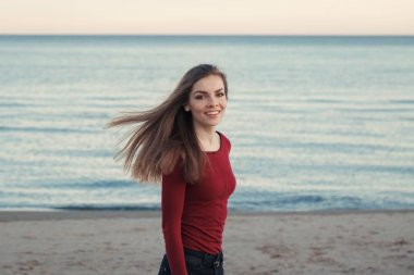 Portrait of happy smiling laughing carefree white Caucasian young beautiful woman with messy long hair on windy day outdoor at sunset on beach by water, looking in camera