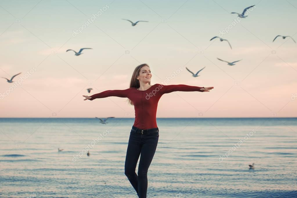 portrait of happy smiling laughing excited Caucasian young woman in jeans running jumping among seagulls birds on autumn fall day outdoor on the shore beach at sunset, lifestyle natural emotion