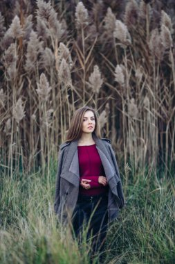 Portrait of pensive sad lonely Caucasian blonde young beautiful woman girl with long hair wearing jeans, coat jacket,  in forest field among large tall plants grass looking in camera