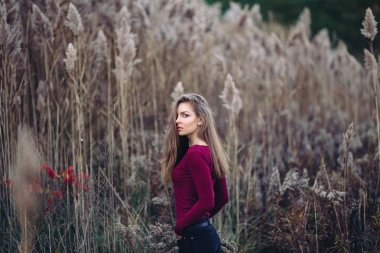 Portrait of pensive sad lonely Caucasian blonde young beautiful woman girl with long hair wearing jeans, red shirt,  in forest field among large tall plants grass looking in camera