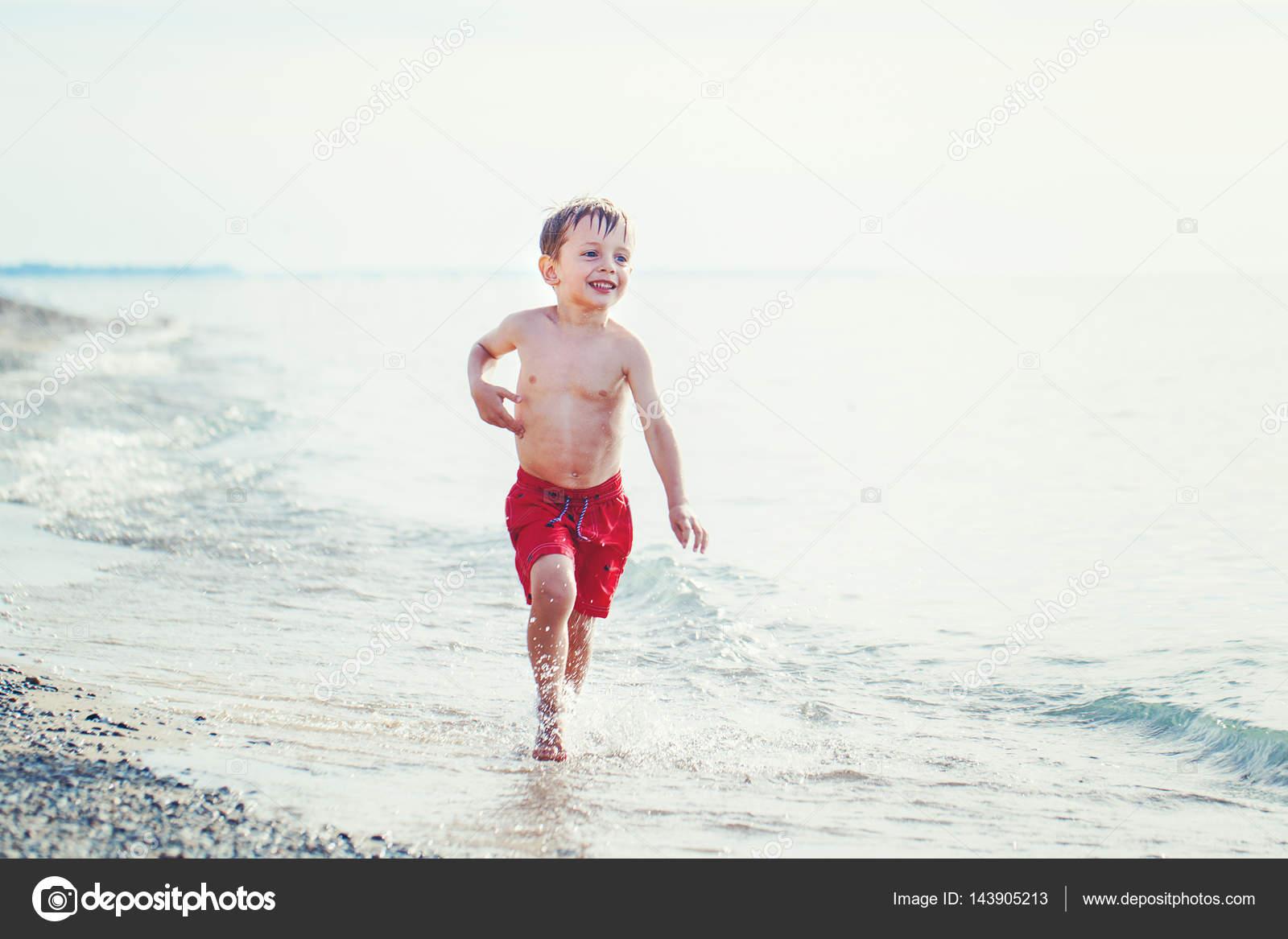 Pantaloncini Da Bagno Ragazzo : Ragazzo in pantaloncini da bagno rosso in esecuzione u foto stock