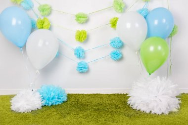 Festive background decoration for first birthday celebration or easter holiday with blue, green and white paper flowers, balloons, fluffy rug on floor with nobody, copyspace for text