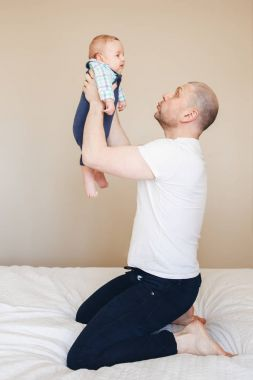 Father taking up newborn baby
