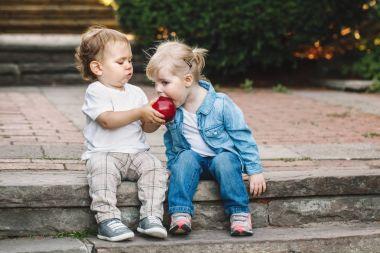 children  sharing,  eating apple
