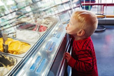 boy looking at ice cream in shop