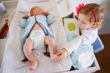 girl toddler helping  changing baby diaper