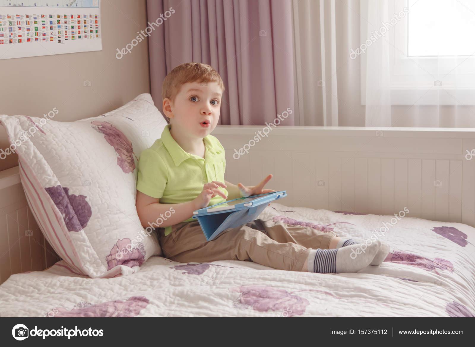 Bett Kleinkind Junge ~ Kleinkind jungen sitzen im bett mit digitalen tisch spielen