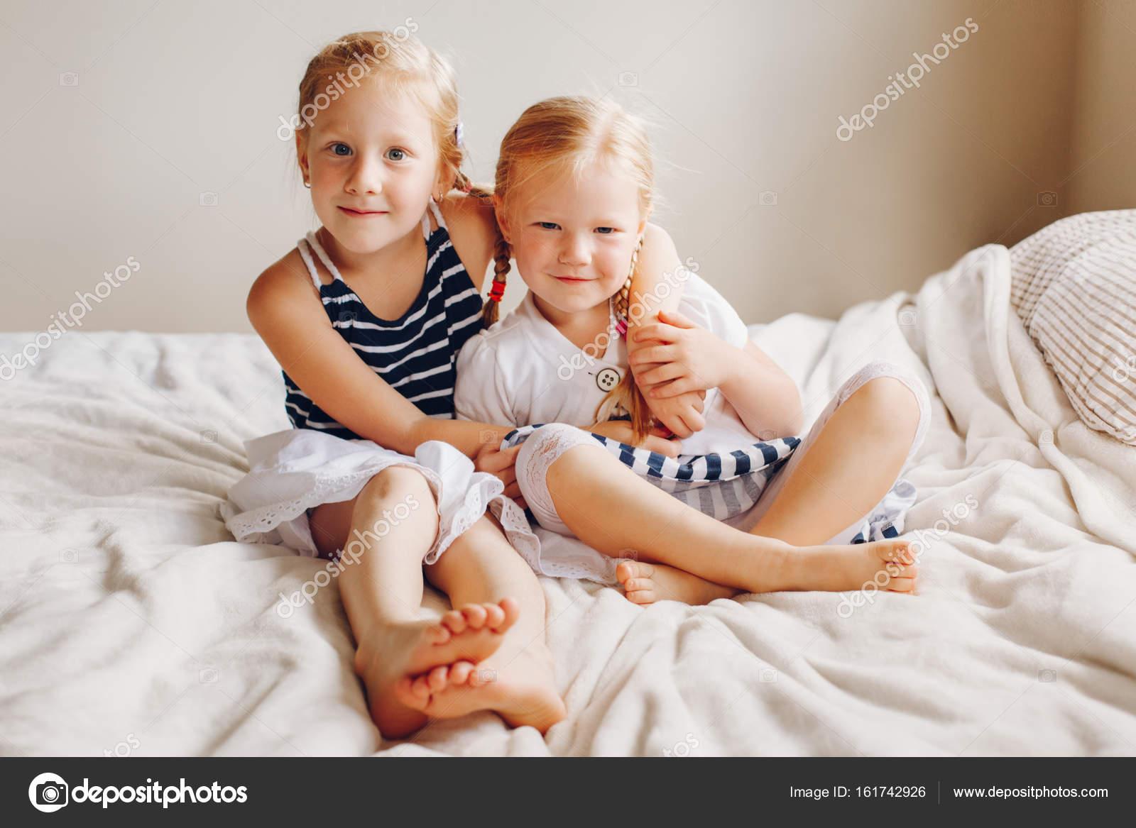 siblings hugging looking in camera stock photo anoushkatoronto