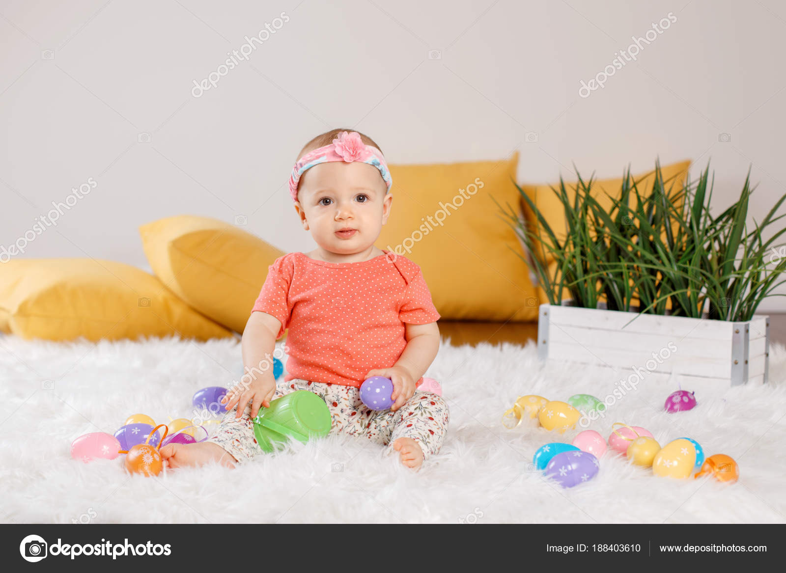 a3ba89377e4 Cute adorable Caucasian baby girl in red onesie t-shirt sitting on white  soft fluffy rug carpet in studio. Kid child playing with Easter colorful  eggs ...
