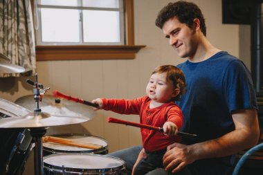 Father teaching baby boy to play drums. Parent with toddler child having fun and spending time together. Dad and kid playing music. Family hobby activity and leisure time.