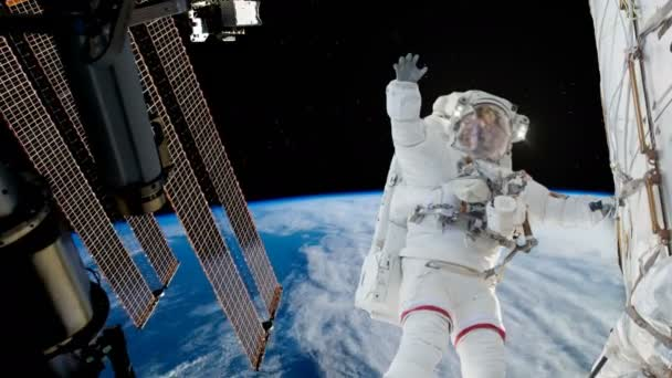 Astronaut working on space station above the Earth. Astronaut Spacewalk, waving his hand in the open space.