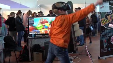 Minsk, Belarus - May 13, 2017: Child with glasses of virtual reality playing a computer game.