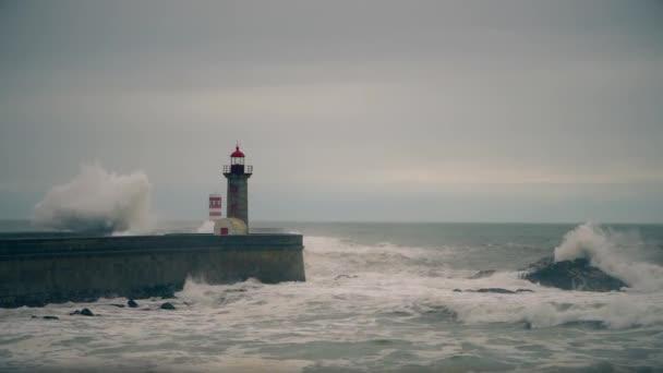 Bouře na pobřeží Atlantiku poblíž starého majáku, Porto, Portugalsko.
