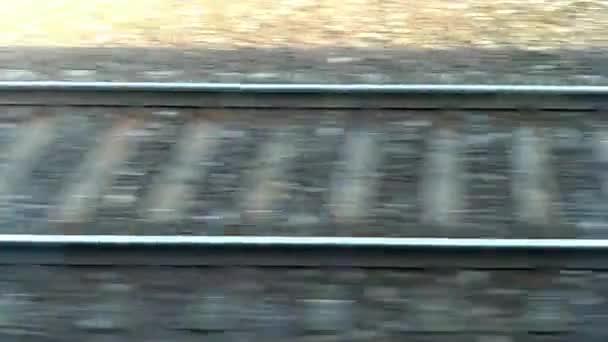 Vlak, kolemjdoucí. Rychle se pohybující železniční tratě. Koleje a pražce rychle prochází