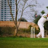Plná délka kriketu hraje na hřišti během slunečného dne, Cricketer na hřišti v akci, Hráči hrají kriket utkání na hřišti