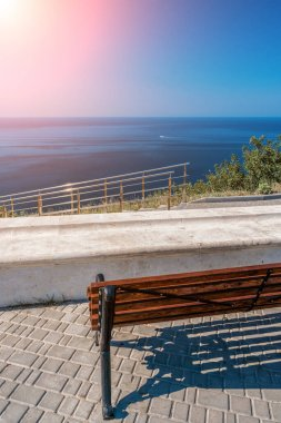Empty bench on sea shore in a park. Sea view from mountain. Travel, relax or loneliness concept. Wooden bench on open space overlooking a beautiful sunny sea view.
