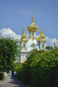 Fotografie Peterhof, Saint Petersburg, Russia. July,18,2014. Tserkovnyy Korpus Bolshogo Dvortsa Peterhof Grand Palace. Church building with golden dome and cupola with orthodoxal cross in top surrounded by