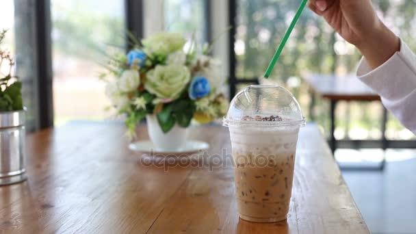 Ženská ruka míchání kávy latte v šálku na dřevěný stůl