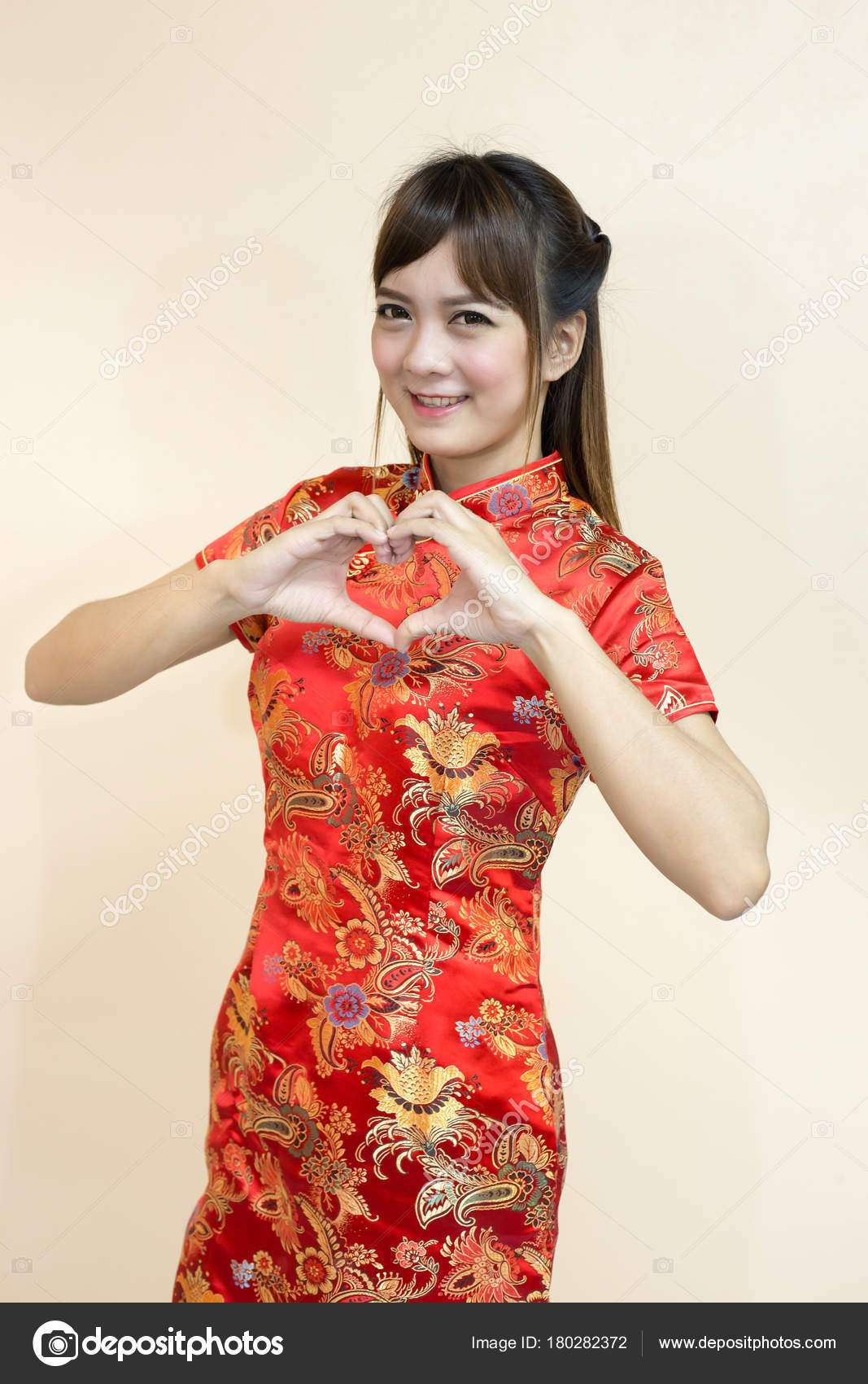 Asian woman greeting traditional chinese cheongsam hand lift welcome asian woman greeting in traditional chinese or cheongsam with hand lift welcome expression and hand is a heart symbol sent love in chinese new year m4hsunfo