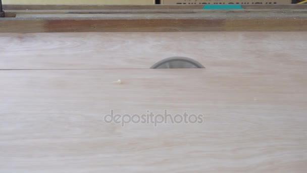 Řezání dřeva nebo překližky v tesařské dílně s stolní kotoučová pila.