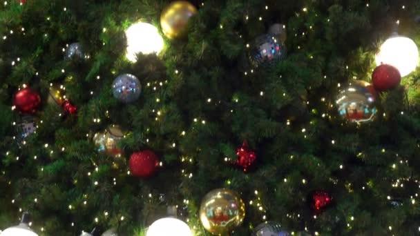 Karácsonyfa díszített fények és ajándékok és arany, ezüst, színes golyók mozog felfelé