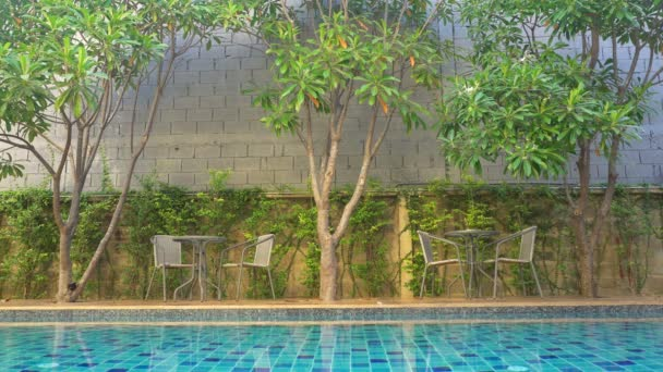 The surface of a swimming pool or water texture Ocean. Which has a table and chair set for relaxing under the tree