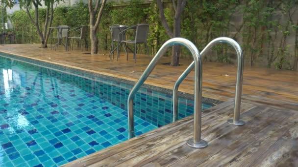 Detail držadla bazénu Povrch bazénu nebo vodní textury Oceán. Který má stůl a židle pro relaxaci pod stromem