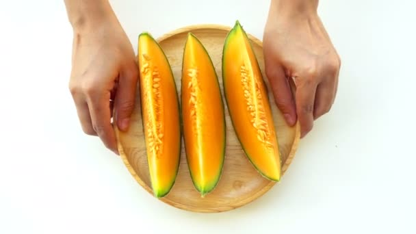 Melon is placed in a ready-to-eat wooden dish that is lifted by hand.