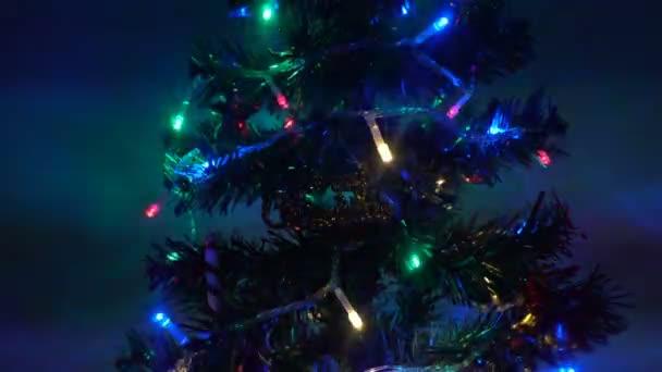 Vánoční stromeček zdobený jasnými světly na oslavách.