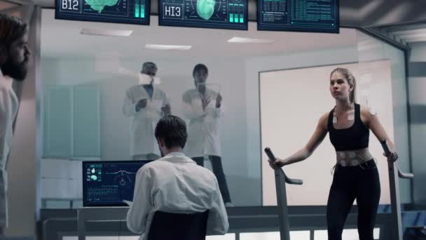 In Science High-Tech Sports Lab Beautiful Athlete Woman walks on treadmill using electrodes attached to her body. Monitors showing ECG and Medical Data Activity. Slow Motion. Shot on Red Epic-W Helium