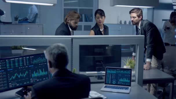 Diverse team of professionals working late at night discussing stock data on computer.. Middle aged employee sitting at his desk uses Desktop and Laptop Computer.