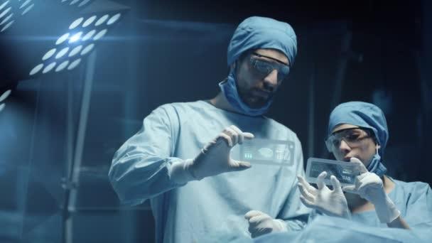 Professionelle Chirurgen und Assistenten analysieren während der Operation die Diagnosedaten der Patienten auf transparenten Telefonen. Moderner Operationssaal im Krankenhaus. Schuss auf rote Epic-W Heliumkamera.