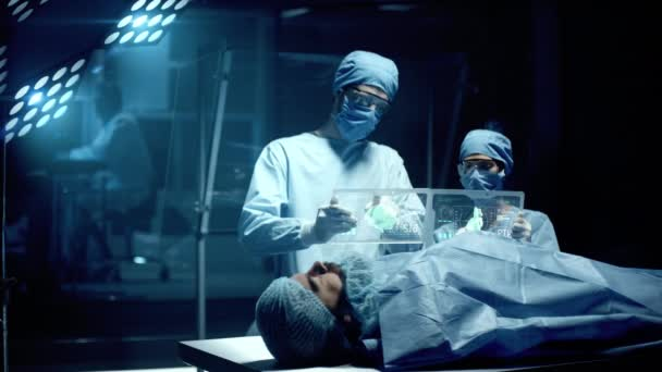 Professional Surgeon and Assistant Analyze Patient Diagnosis Data on Transparent Tablets During Surgery. Patient lying down on Modern Hospital Operating Table. Shot on RED Epic-W Helium Camera.