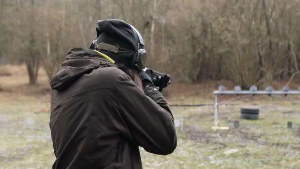 A fickó vadászpuskával lő a lőtéren lévő célpontokra..