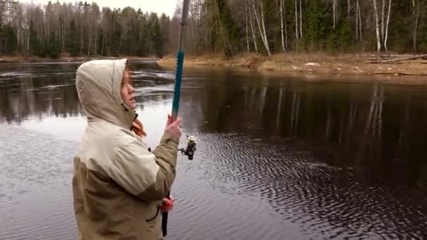 dívka rybář v kapuci hodí rybářský prut do řeky chytit ryby