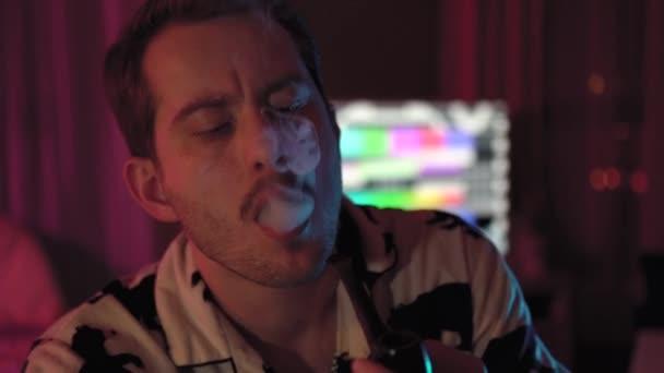Nahaufnahme eines Mannes, der eine Pfeife raucht. Ein Mann mit Schnurrbart und Stoppelbart. das Zimmer hat farbige Beleuchtung, rosa und blau.Er sitzt auf einem Hocker am Tisch.Verführerisch Meinung und Gedanken.Viel Rauch