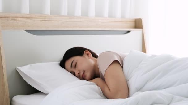 Ázsiai fiatal nő aludt az ágyban, és mozgott az arcát, és élvezi az egészséges alvás reggel.