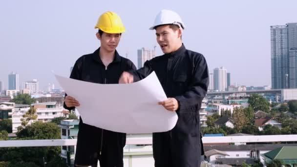 Dva stavební inženýři držící na staveništi plán a hovořící o stavebním projektu.