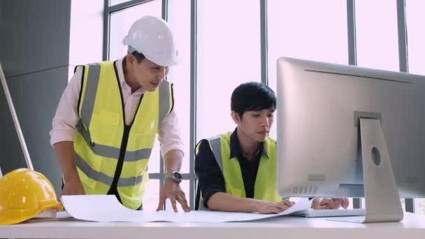 Stavební inženýr mluvit s kreslení zaměstnanců řešit strukturální problémy nové kancelářské budovy.