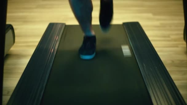 Male legs in sneakers run on an orbitrek-simulator. Close up