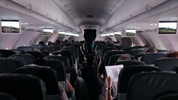 Cestující sedí a spí v letadle.