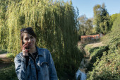 Lady in a blue jacket and jeans talking on the phone in a spring park over a creek bridge and a weeping willow at the background