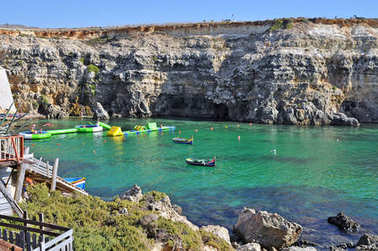 Bay of the island of Gozo with rocks and turquoise sea and playing with people