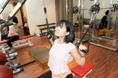 Asian woman doing muscle training with equipment in personal gym