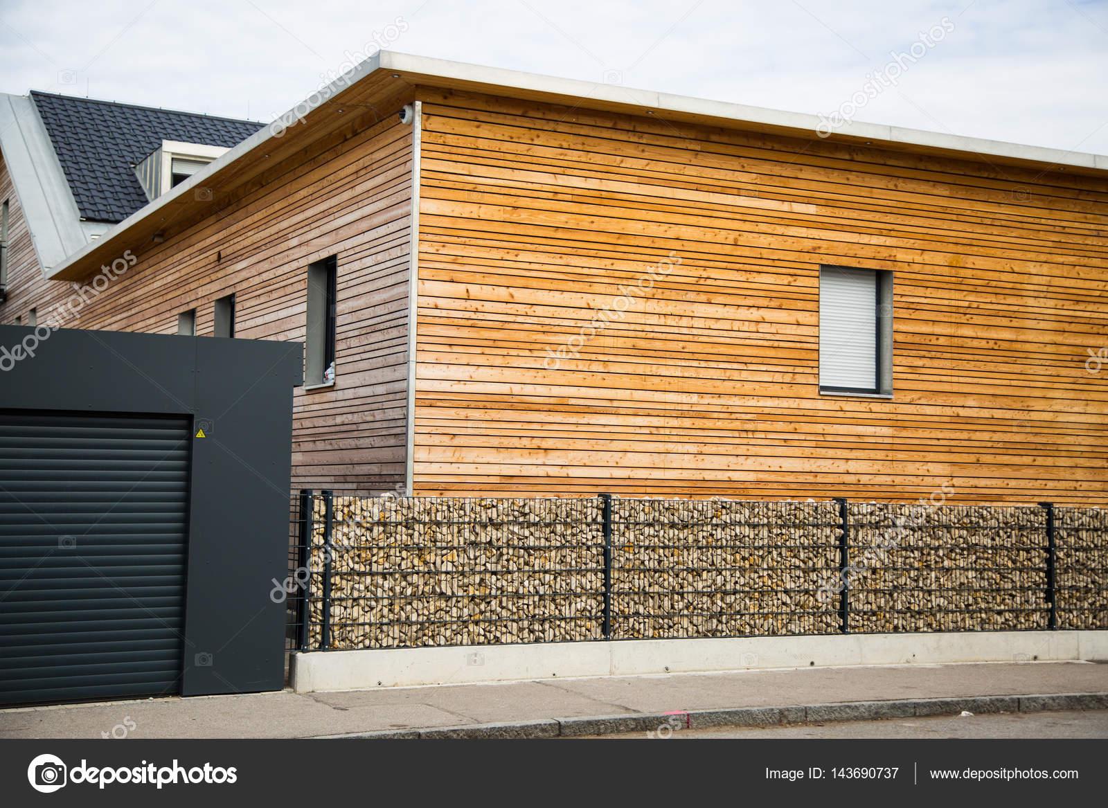 Casa moderna in legno con recinto di pietra nella parte for Casa moderna legno